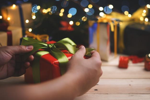 Mano che lega regalo di regalo di natale verde rosso