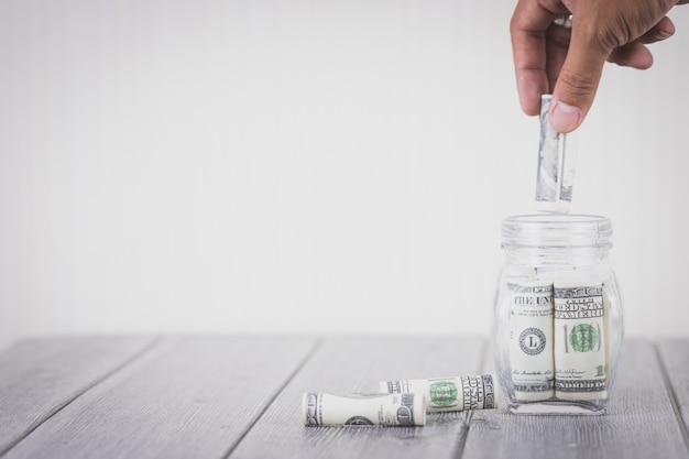Mano che mette i soldi dollari in bottiglia di vetro, concetto di risparmio di denaro, investimento aziendale