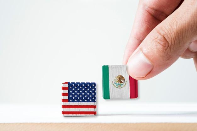 Mano che mette lo schermo della stampa bandiera del messico e cubano di legno della bandiera di usa è simbolo del conflitto per entrambi i paesi nell'immigrato messicano
