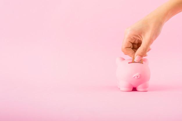 Mano che mette moneta nel porcellino salvadanaio rosa
