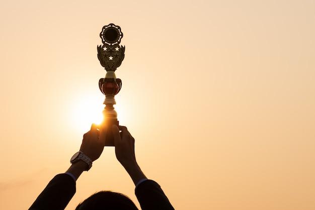 Mano che mostra il trofeo vincente del premio d'oro durante il tramonto. concetto di successo aziendale.