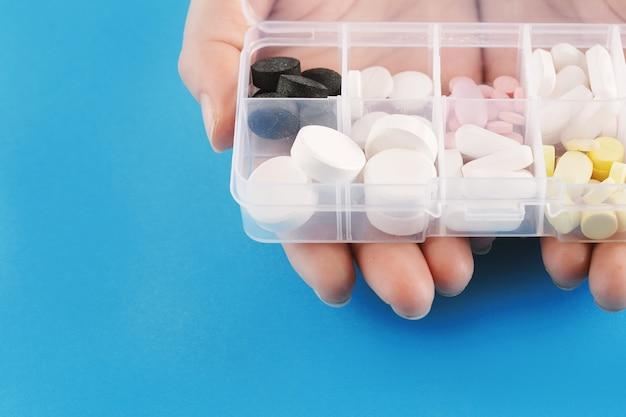 Mano che mostra la scatola della medicina con le pillole