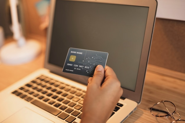 Mano che mostra una carta di credito accanto a un computer portatile mock up