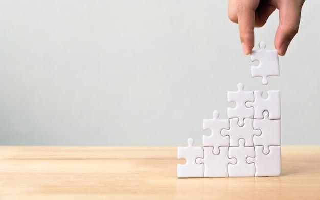 Mano che organizza jigsaw puzzle accatastamento come scala sul tavolo di legno