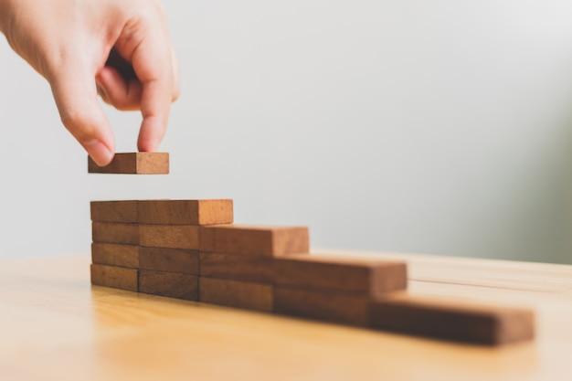 Mano che organizza l'impilamento del blocco di legno come gradino. concetto del percorso di carriera della scala per il processo di successo di crescita di affari