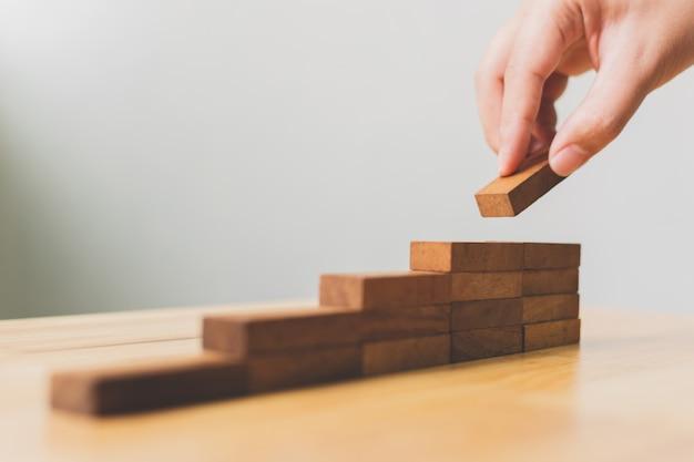 Mano che organizza l'impilamento del blocco di legno come gradino