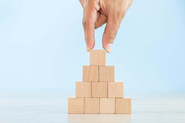 Mano che organizza l'impilamento del blocco di legno come scala a gradini, con il concetto di un'azienda fiorente che va per il successo.