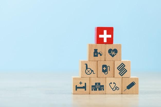 Mano che organizza l'impilamento del blocco di legno con l'icona di assistenza sanitaria medica.