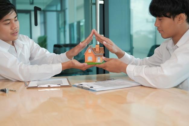 Mano che protegge il modello di casa. assicurazione sulla casa, sicurezza.