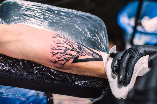 Mano che pulisce il tatuaggio fresco sul braccio