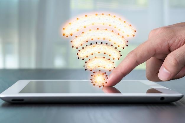 Mano che punta a tablet con segnale wifi. concetto di tecnologia.