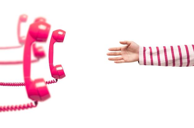 Mano che raggiunge il telefono rosa