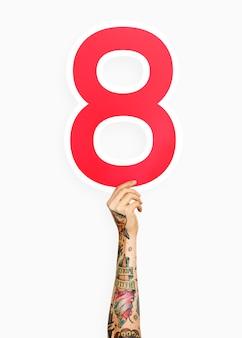 Mano che regge il numero 8
