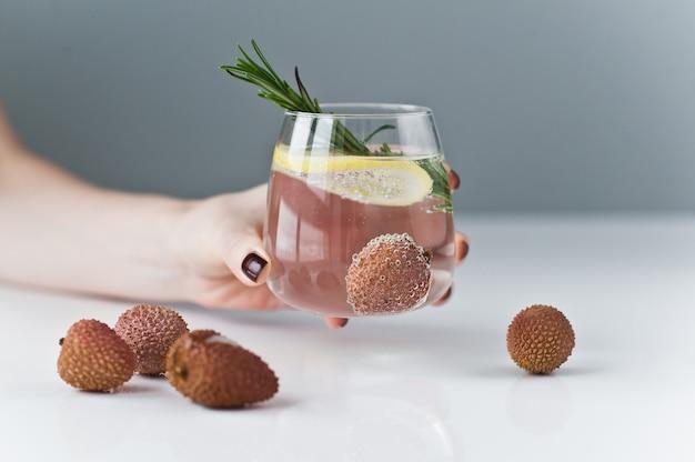 Mano che regge un bicchiere di acqua limpida con limone, rosmarino, litchi.