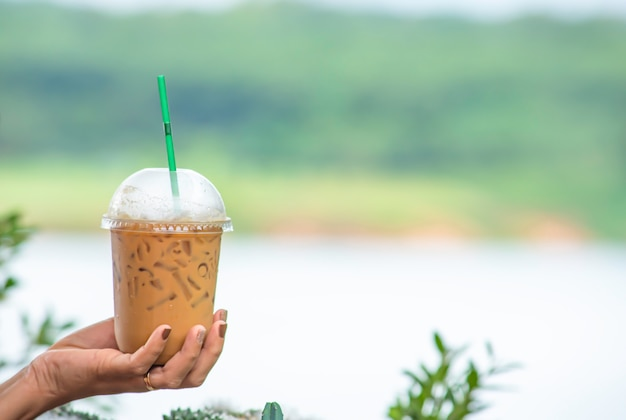 Mano che regge un bicchiere di caffè espresso freddo sfondo sfocato vista albero e acqua.