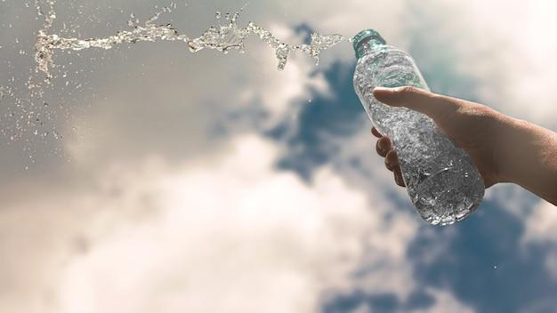 Mano che regge una bottiglia di plastica trasparente di pura acqua potabile rinfrescante e splash