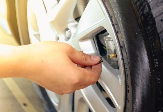 Mano che rimuove un pneumatico nero. controllare la pressione dell'aria dei pneumatici.