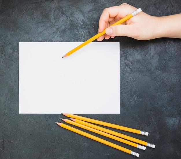 Mano che schizza sul libro bianco in bianco con una matita su sfondo nero