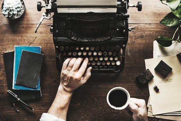 Mano che scrive il retro scrittore del lavoro a macchina della macchina da scrivere