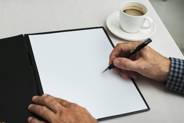 Mano che scrive in carta bianca accanto alla tazza di caffè