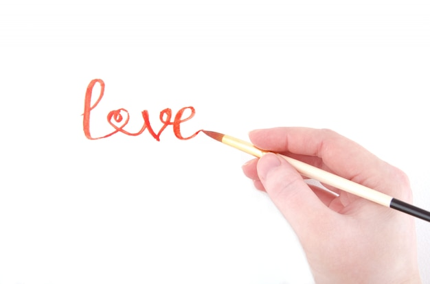 Mano che scrive la parola amore (con una delle lettere a forma di cuore)
