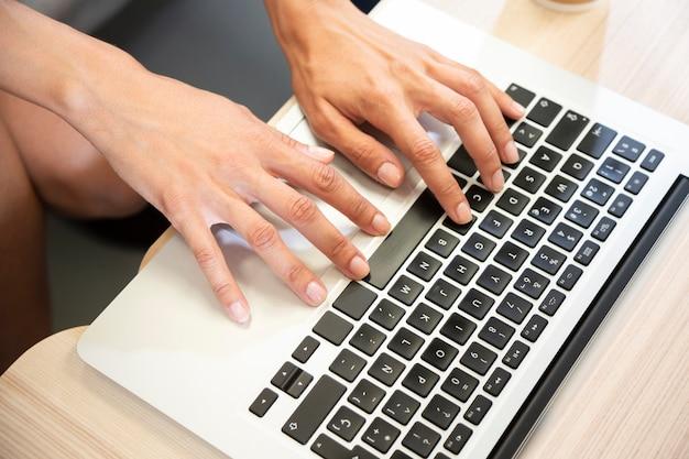 Mano che scrive sulla vista superiore del computer portatile
