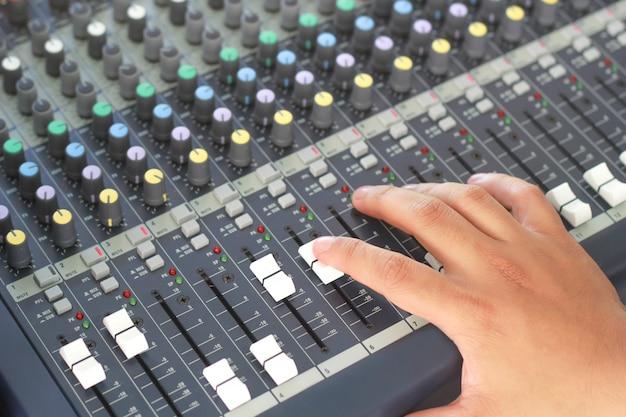 Mano che sposta il livello sul mixer audio.