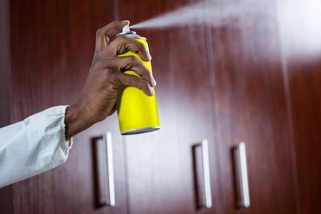 Mano che spruzza pesticida da una bomboletta spray