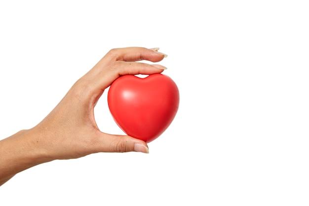 Mano che tiene a forma di cuore rosso
