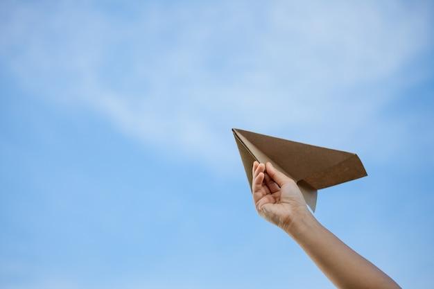 Mano che tiene aeroplano di carta contro il cielo