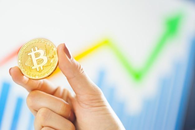 Mano che tiene bitcoin dorato