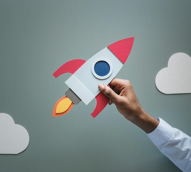 Mano che tiene business startup rocketship