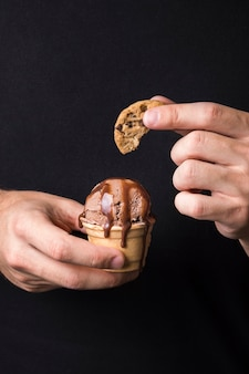 Mano che tiene delizioso gelato con biscotto