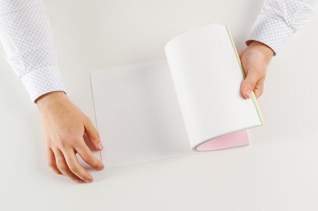 Mano che tiene derisione del libro aperto in bianco su