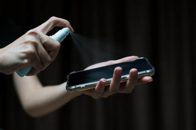 Mano che tiene e pulisce lo schermo del telefono cellulare con spray alcol isopropilico per protezione da virus corona o covid-19.