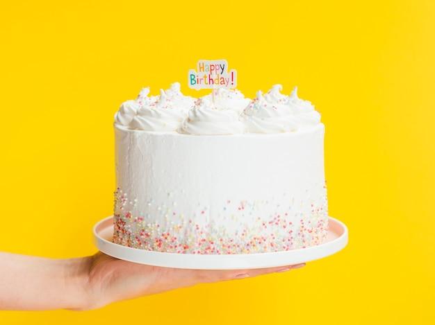 Mano che tiene grande torta di compleanno bianca
