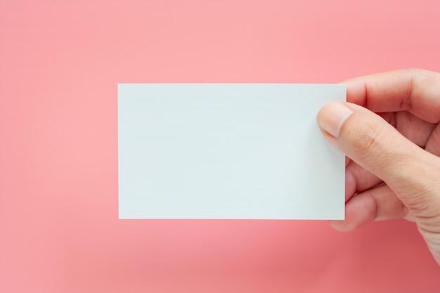 Mano che tiene i biglietti da visita in bianco su sfondo rosa