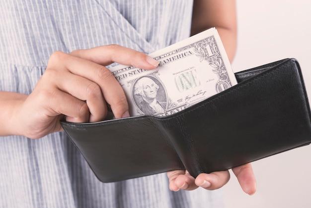 Mano che tiene i soldi del dollaro con portafoglio su sfondo bianco.