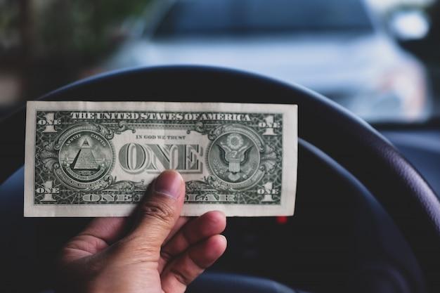 Mano che tiene i soldi del dollaro in auto