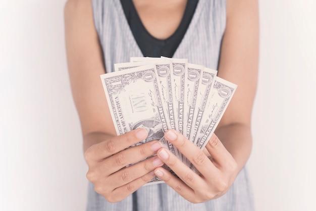 Mano che tiene i soldi del dollaro su sfondo bianco.