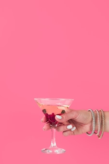Mano che tiene il bicchiere da cocktail con spazio di copia