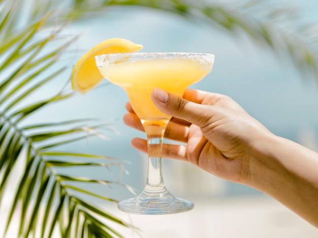 Mano che tiene il bicchiere da cocktail freddo arancione con bevanda rinfrescante