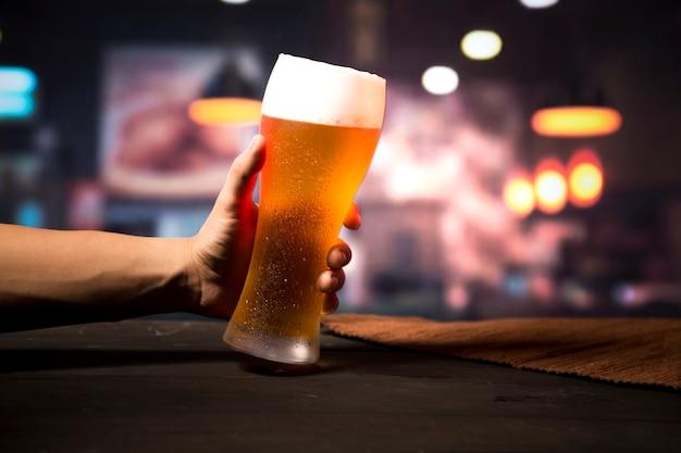 Mano che tiene il bicchiere di birra