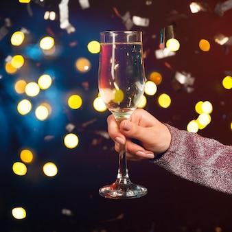 Mano che tiene il bicchiere di champagne con coriandoli ed effetto bokeh