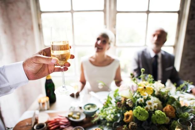 Mano che tiene il bicchiere di champagne