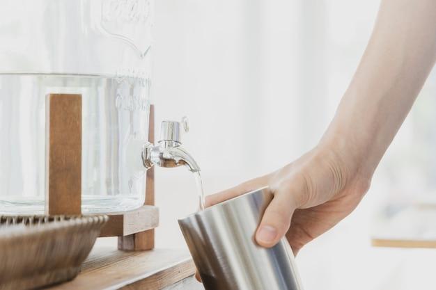 Mano che tiene il bicchiere in acciaio inossidabile durante il riempimento di acqua potabile.