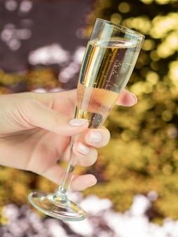 Mano che tiene il bicchiere pieno di champagne frizzante