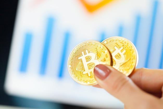 Mano che tiene il bitcoin dorato