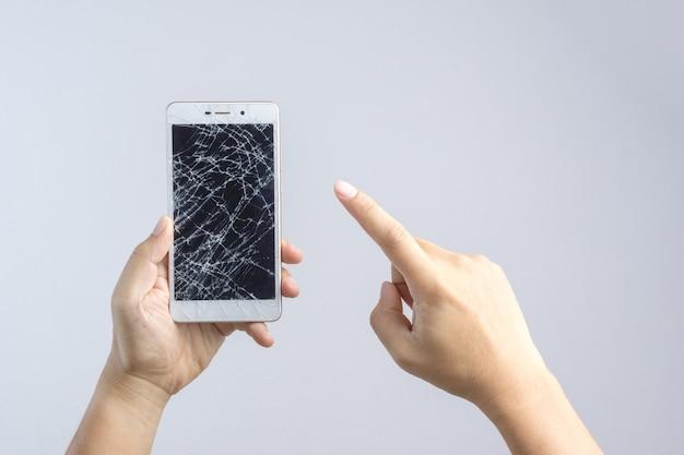 Mano che tiene il cellulare con schermo rotto