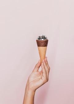Mano che tiene il cono gelato